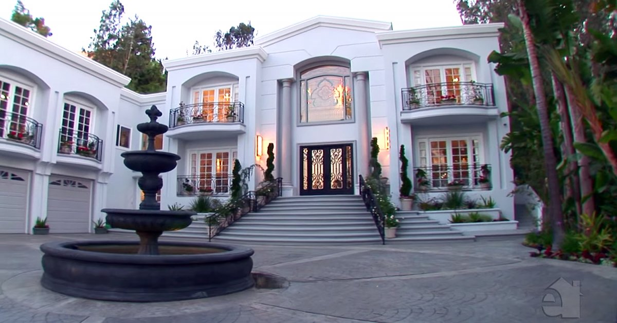 the-entrance-is-two-stories-high-with-a-fountain-centered-in-the-driveway
