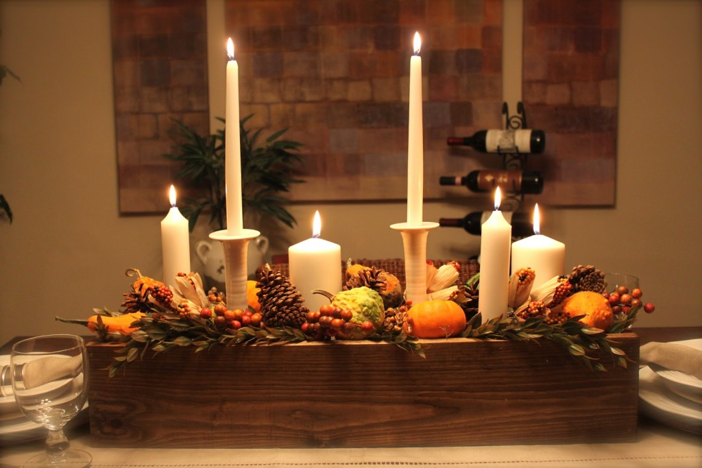 good-looking-thanksgiving-table-centerpiece-decor_white-tapper-candle_brown-pine-cone_pumpkin-ornament_brown-rustic-wood-holder_white-candle-holder_wine-rack