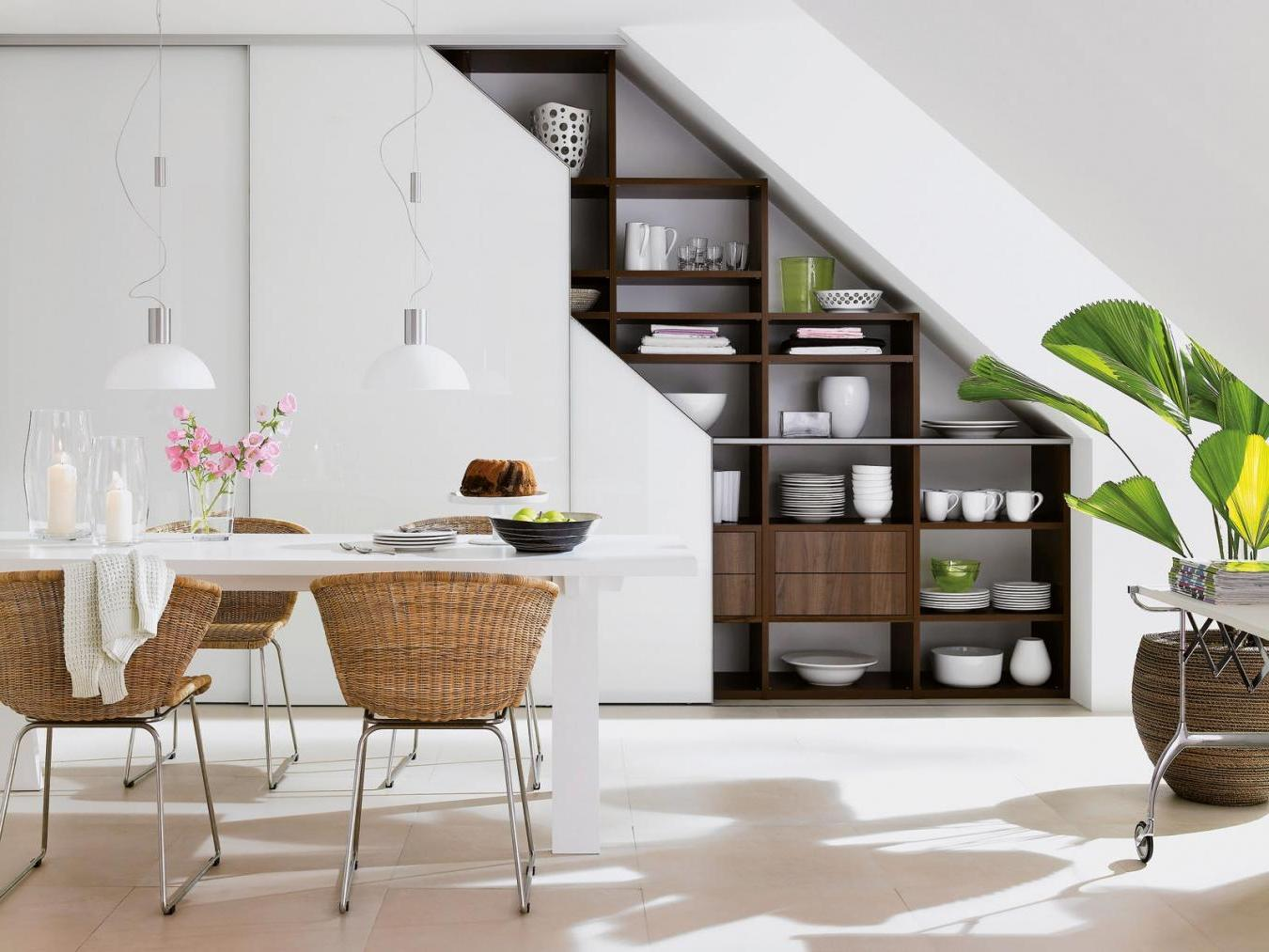 Nice-wooden-shelving-for-dining-set-under-the-staircase-along-with-a-delicate-dining-space-with-white-table-and-rattan-chairs