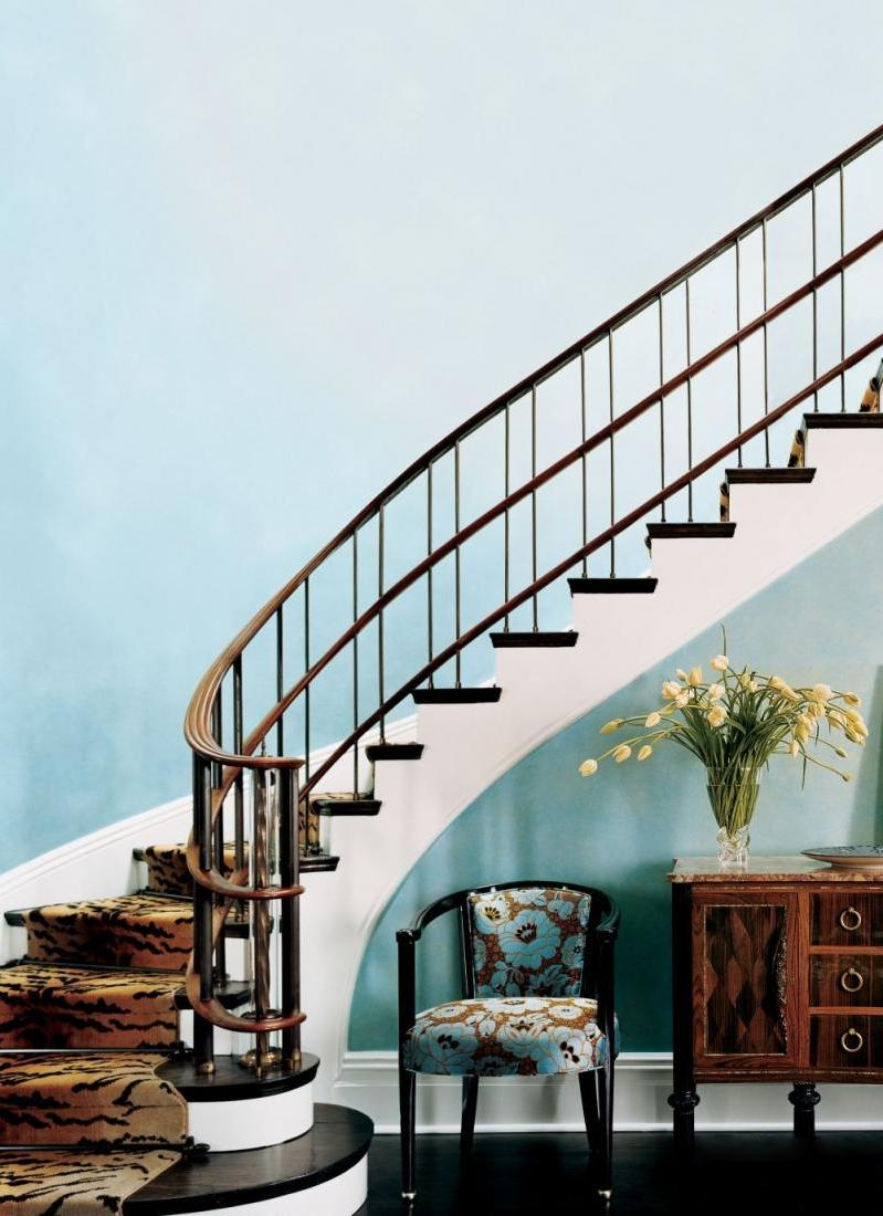 Pretty-vintage-armchair-and-wooden-armoire-under-the-staircase-decortaed-by-fresh-flowers-and-blue-wall-color