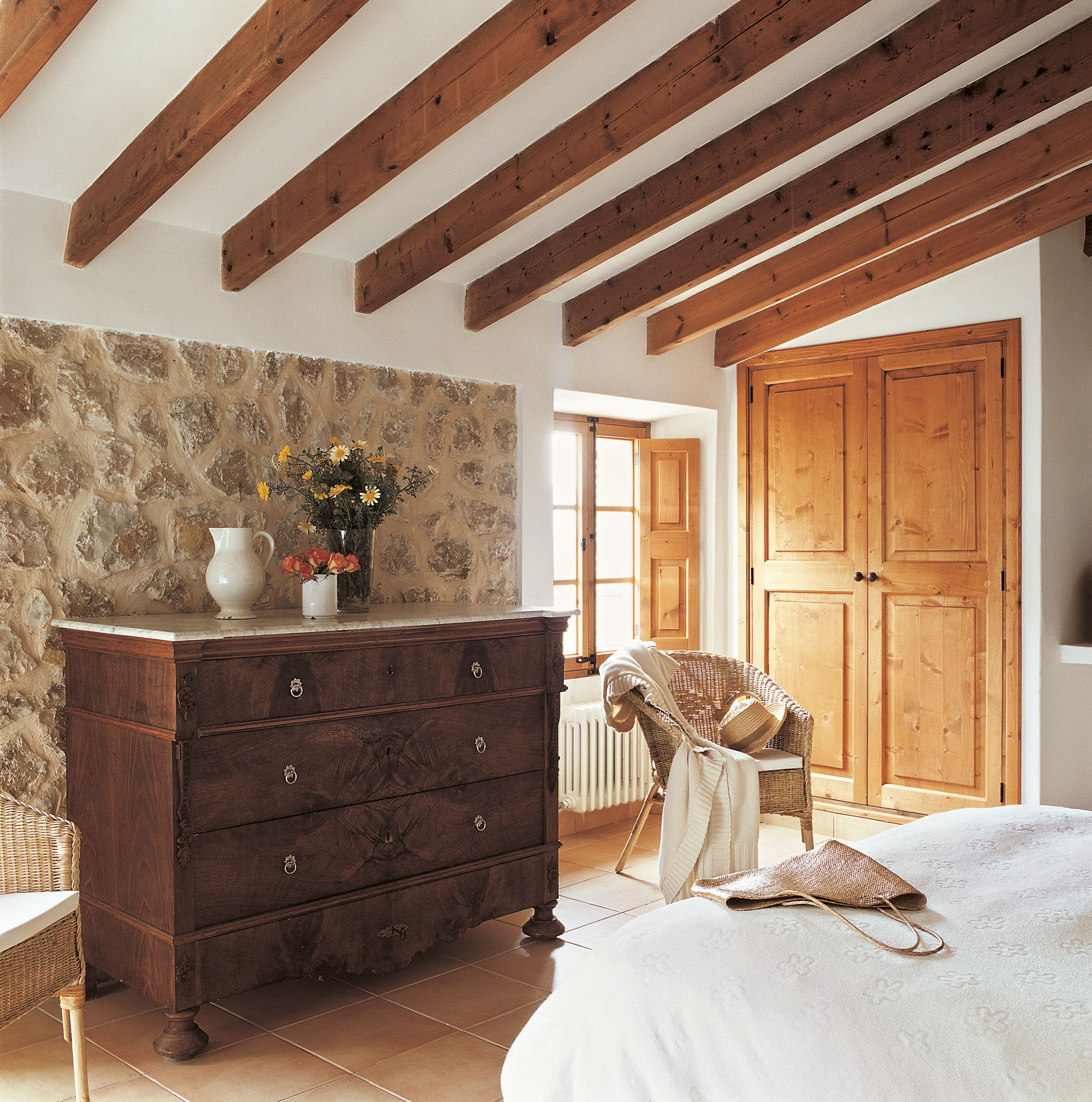 comoda-en-dormitorio-rustico-con-pared-de-piedra-y-vigas-vistas_4e8cf37b