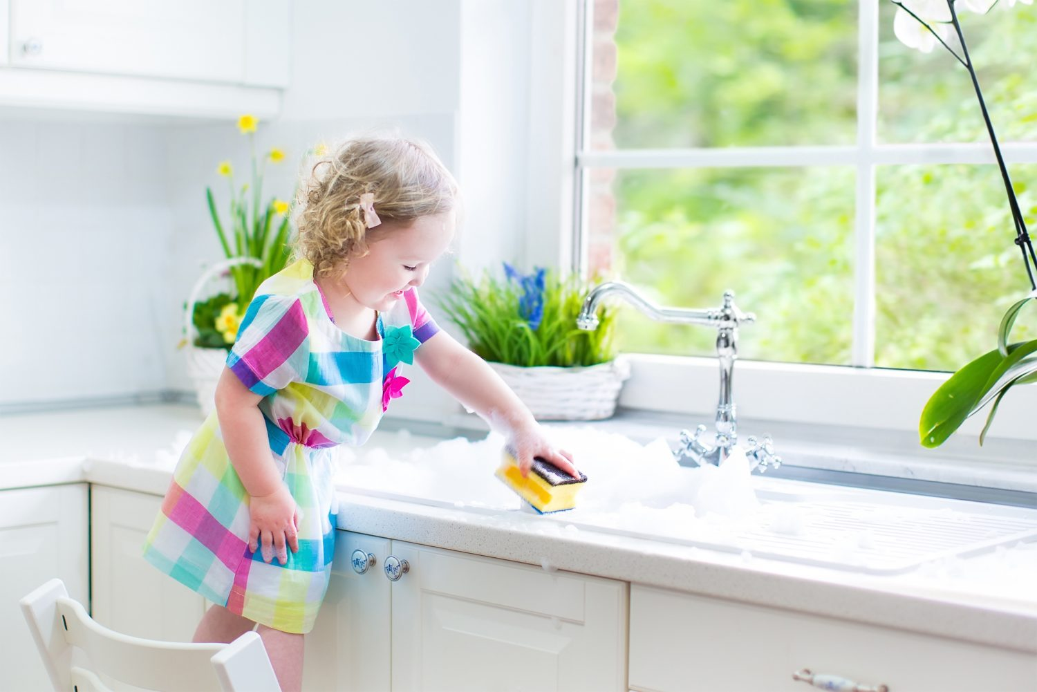 Cute toddler girl in colorful dress cleaning table on kitchen