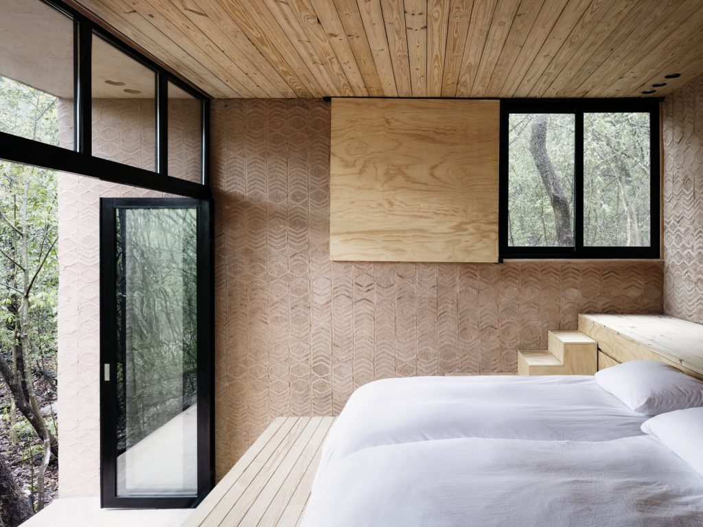 rammed-earth-brick-and-wood-give-the-bedroom-a-warm-rustic-atmosphere