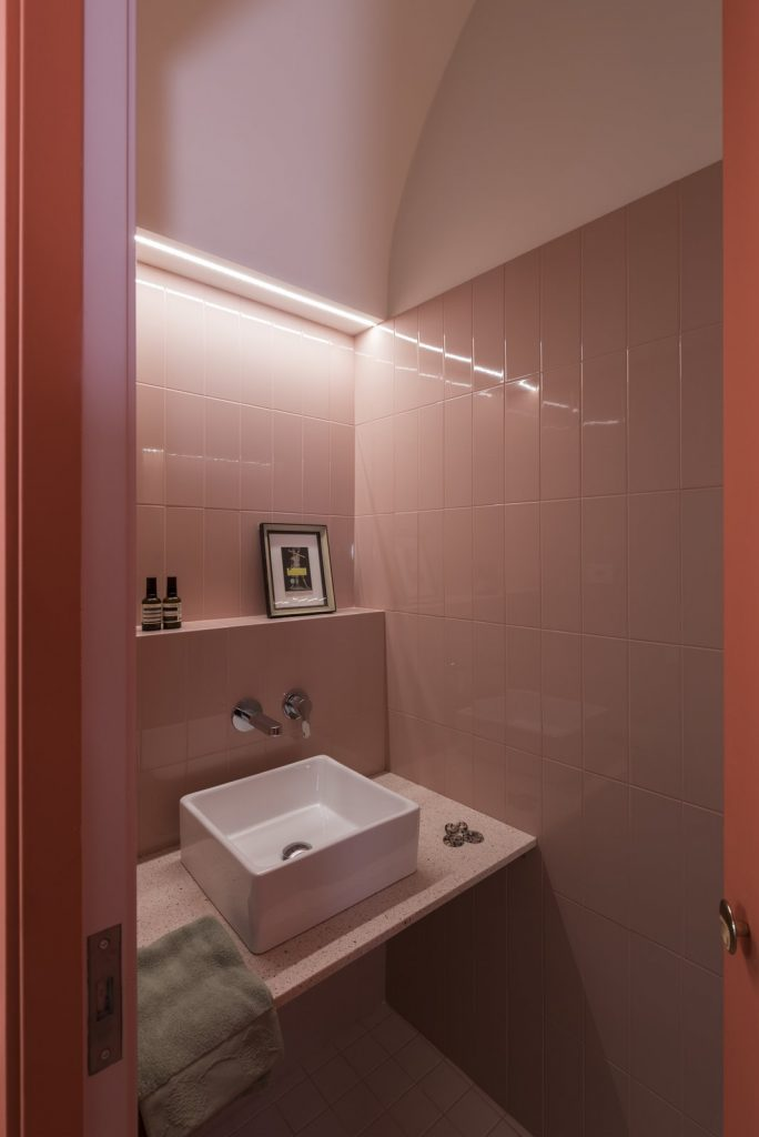 the-guest-bathroom-sits-hidden-in-a-coral-colored-arch-volume-off-the-kitchen